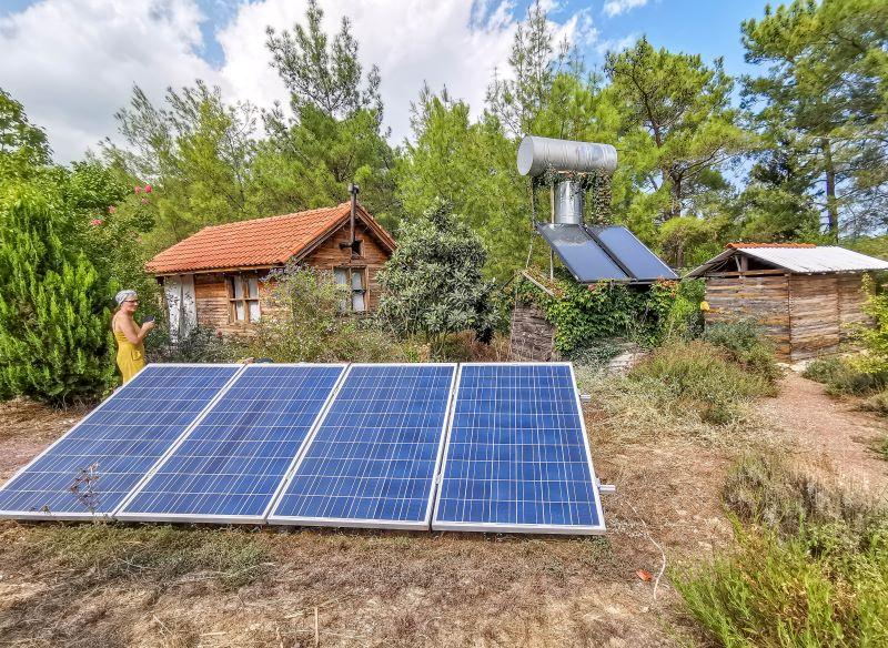 Arkada misafirhane, yanında tuvalet ve duşlar, ortada elekrik için güneş panelleri